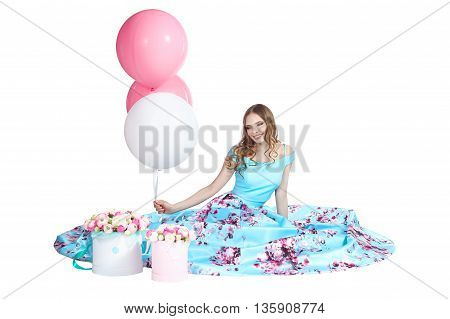 Young beautiful girl with a bright bouquet of paper flowers sitting on the white background, looking up and smiling.