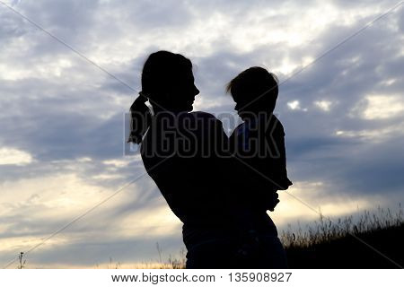 Silhouette of a girl with a baby in the evening on the nature
