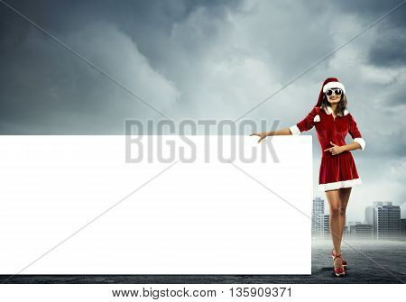 Christmas Santa girl pointing with finger on white blank banner