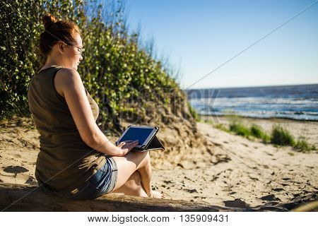 Woman in glasses using digital tablet at sunny sea stone coast. Freelance and rest concept.