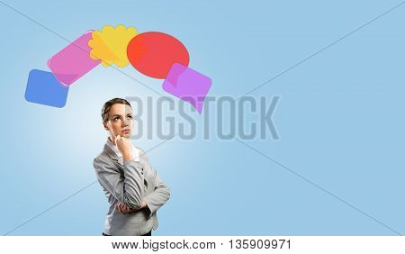 Young thoughtful businesswoman and colorful speech bubbles above head