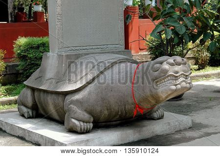 Chengdu China - April 23 2005: A large carved stone turtle with a red ribbon around its neck at the base of a column in the Qing Yang Palace courtyard