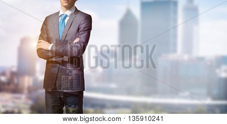 Close up of businessman with arms crossed on chest on modern city background