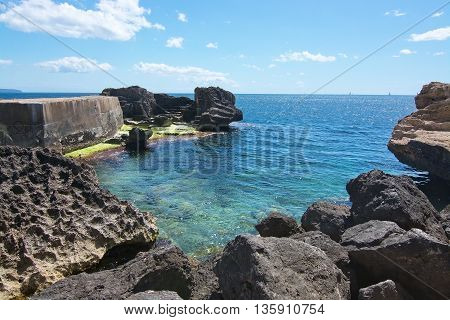 Rocky landscape with green seagrass water and concrete pier on a sunny day in Molinar Mallorca Spain.