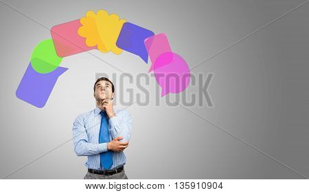 Young thoughtful businessman and colorful speech bubbles above head