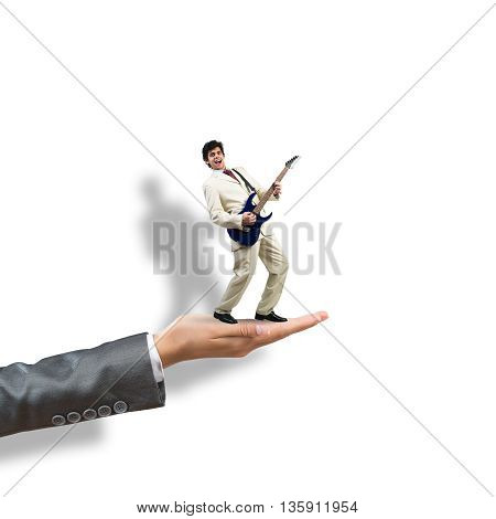 Big female palm on white background holding small confident businessman play guitar