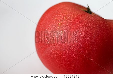 ripe tomato in the drops of water close-up