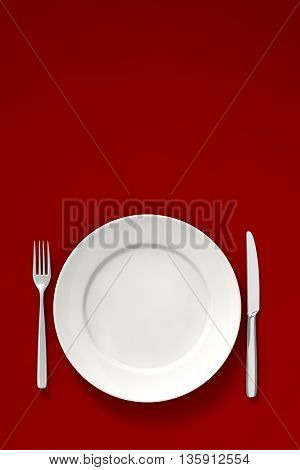 A white dish fork and knife on a red dinner table