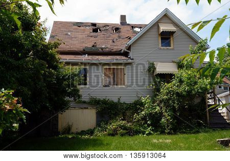 Large holes exist in the roof of an abandoned house, falling apart near downtown Joliet, Illinois.