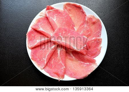Fresh sliced pork on white dish with black leather background for Japanese hot pot.