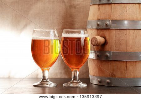 Two glasses of beer near wooden barrel on canvas background