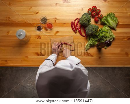 Female Chef Cutting Pepper On Wooden Cutting Board, Top View