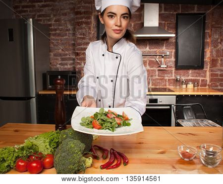 Woman Cook With Fresh Salad In Her Hands In Kitchen