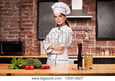 Woman Cook Standing In The Kitchen In White Cook Uniform.