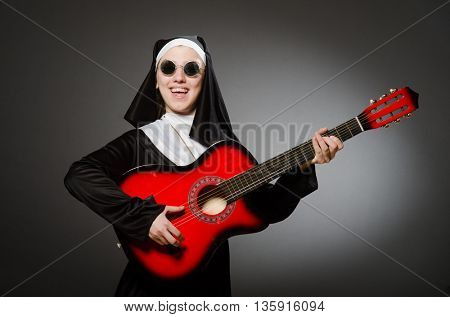 Funny nun with red guitar playing