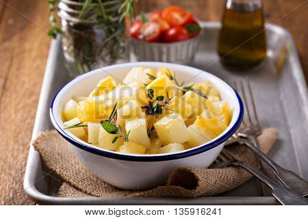 Potato with melted cheese and herbs prepared on a grill