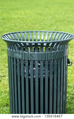 vertical picture of a trash can in a public park