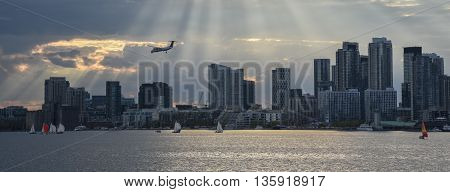 TORONTO SKYLINE WITH AIRPLANE AND SUNBEAMS IN THE DISTANCE
