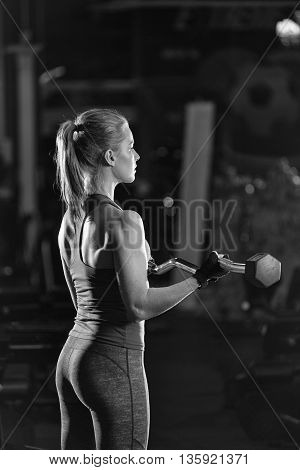 Beautiful sporty woman doing power fitness exercise at sport gym. Girl with dumbbell. Black and white.