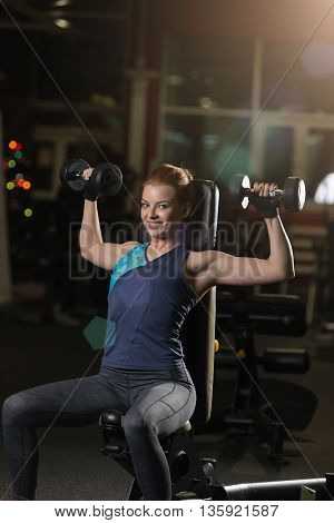 Beautiful sporty woman doing power fitness exercise at sport gym. Girl with dumbbell on black.