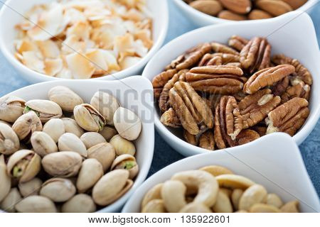Variety of nuts in small white bowls healthy snacks
