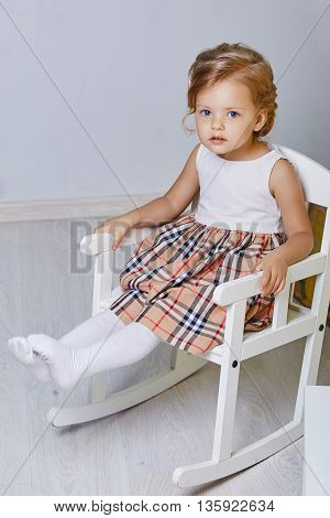 Beautiful little girl.Blue-eyed blonde.White chair.Children's room. Happy small girl portrait.