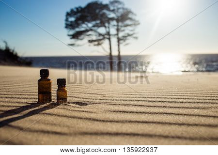 Essential pine oil on sand at sunset with beautiful copy space - sea coast and pine tree in background. Concept advantage and energy of natural essential oils