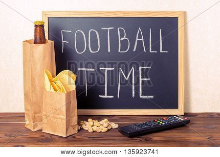 Football Fans Concept Of Beer Bottle In Brown Paper Bag,  Chips, Pistachio, Tv Remote Control And Ha