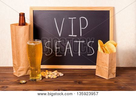 Football Fans Concept Of Beer Bottle In Brown Paper Bag, Glass, Chips, Pistachio And Handwriting Tex