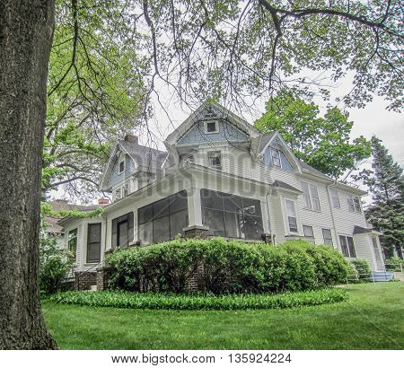 White Victorian house with veranda on manicured green lawn in Midwestern town.