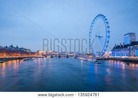 London Eye at night with river Thames in London, UK. At a height of 135 meters, London Eye is the tallest Ferris wheel in Europe.