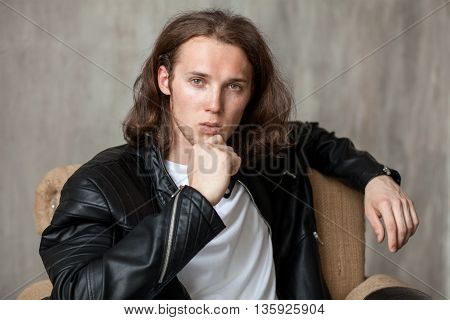 Young Long-haired Hunk With Bristle In Imposingly Pose