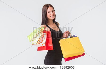 Happy shopping. Young woman in black dress holding multicolored shopping bags