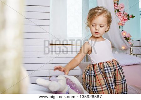 Beautiful little girl playing with soft rabbit.Blue-eyed blonde.Children's room. Happy small girl portrait.