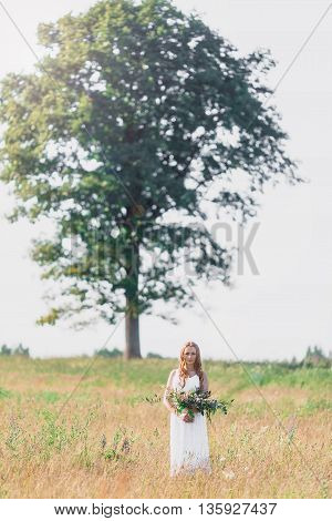 Beautiful young woman on the background of a large tree with a bouquet of flowers in their hands, sunset