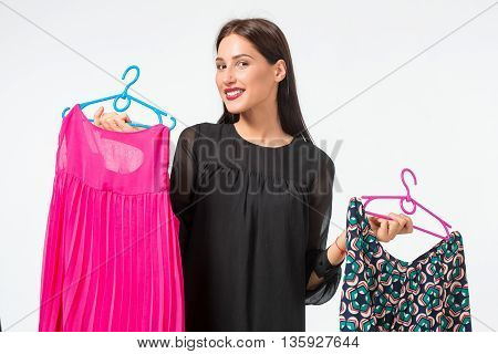 beautiful young woman choosing dresses on white background