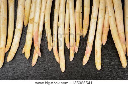 White raw asparagus on black background .
