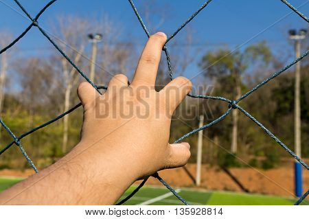 Close up of hand grab the rope mesh fence