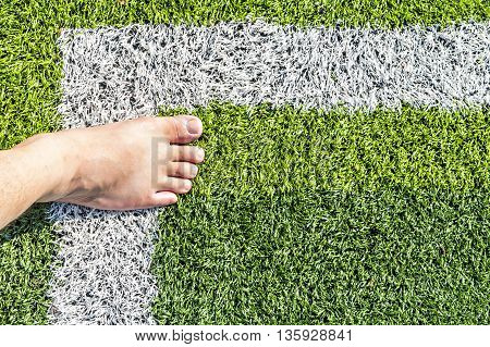 Barefoot standing on artificial turf with copy space