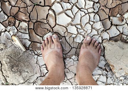 Barefoot standing on dry and cracked ground conservation concept dramatic style