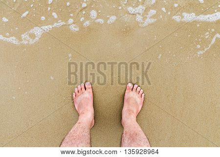 Top down view of feet on the beach with copy space