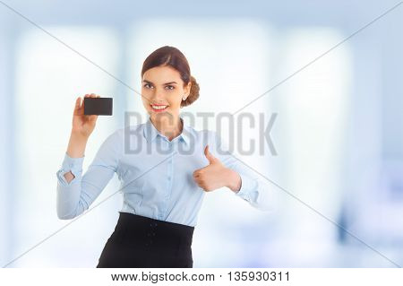 Portrait of happy smiling young beautiful businesswoman showing something on card or blank copyspase for product or sign text, making thumb up and saying Ok. Blue background.