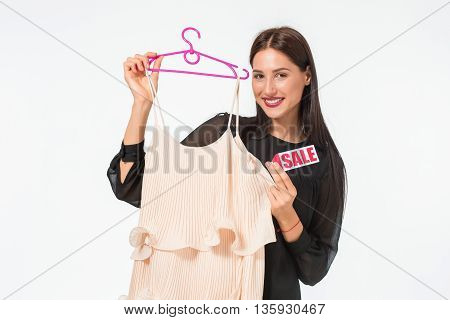 beautiful young woman choosing dresses on white background. hold beige clothes with sale sign
