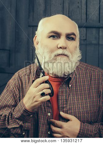 Old bearded man with serious face. Hairdresser with scissors cutting long grey beard in checkered shirt with scissors making new style on wooden wall background