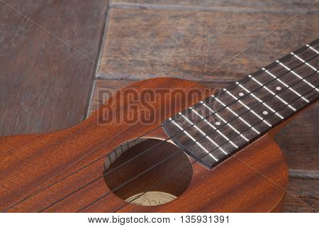 A closeup photo of an ukulele on wooden background