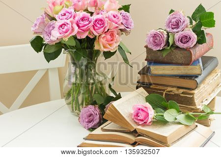 Pile of old books with bouqet of pink rose flowers