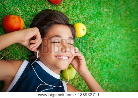 Portrait of a cute smiling teen boy listening to music, lying down on a fresh green grass field, happy summer weekend, spending time outdoors