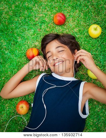 Portrait of a cute smiling teen boy listening to music, lying down on a fresh green grass field, happy summer weekend