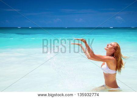 Cheerful female on the beach, splashing refreshing water, enjoying summer holidays on the beach resort, happy active lifestyle
