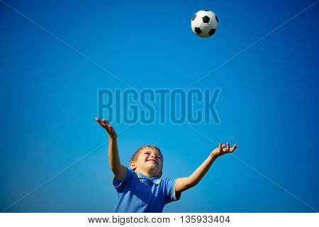 Happy boy playing ball, cute little child catching ball over blue sky background, playing football in sunny summer day, happy healthy childhood